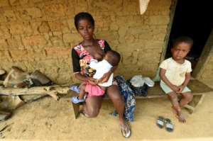 Yvonne Ndep, an 18-year-old pregnant Cameroonian, breastfeeds her child at a house in Bashu. Thousands have fled to the remote Nigerian village after Cameroon launched a crackdown on anglophone separatists
