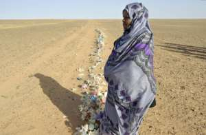 Zghala, a Saharawi woman, looks at Moroccan soldiers in the Al-Mahbes area as she accompanies her 14-year-old son to show him the wall separating the Polisario controlled Western Sahara from Morocco on February 3, 2017