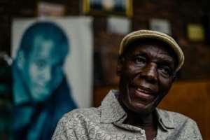 Zimbabwe music icon Oliver 'Tuku' Mtukudzi, pictured in January 2018. Over his shoulder is a portrait of his late son, Sam Mtukudzi.  By Jekesai NJIKIZANA (AFP)