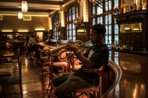 A musician plays at the bar of the Rand Club, the imposing Edwardian-style club in Johannesburg's vibrant centre.  By MARCO LONGARI (AFP)