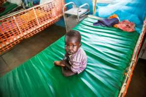 A malnourished child sits on a bed at the MSF clinic in Aweil. The MSF unit for malnourished children suffering from complications such as acute respiratory infections or diarrhoea, is already full