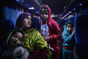 A Malian migrant woman with her children is transferred by bus to a temporary shelter upon their arrival in Bamako after being repatriated from Libya by the IOM.  By MICHELE CATTANI (AFP/File)