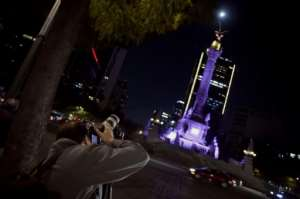A man taking pictures of the Super Moon during the start of the total lunar eclipse, at the Angel de la Independencia in Mexico City.  By ALFREDO ESTRELLA (AFP)