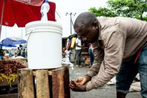 A man washes his hands with chlorinated water at Mabibo market in Dar es Salaam.  By Ericky BONIPHACE (AFP)