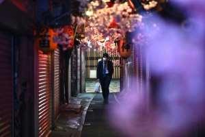 A man wearing a face mask walks along Omoide Yokocho in Tokyo.  By Philip FONG (AFP)