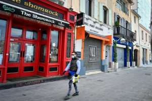 A man wearing a face mask walks past closed bars and restaurants in Marseille, southern France.  By GERARD JULIEN (AFP)