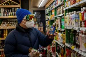 A man wearing a mask, goggles and gloves buys beverages at a supermarket in Beijing.  By NICOLAS ASFOURI (AFP)