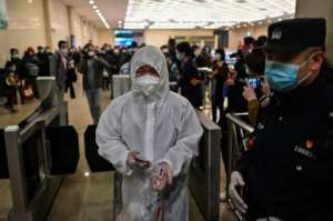 A man wearing a protective suit arrives at Hankou Railway Station in Wuhan to board one of the first trains leaving the city. By Hector RETAMAL (AFP)