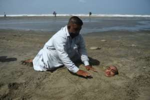 A man buries his paralysed son in sand on a beach in Karachi during the eclipse. Folklore has it if the eclipse passes over them they will be cured.  By Rizwan TABASSUM (AFP)