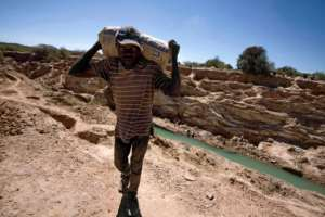 A man carries a bag at a mine for copper and cobalt in another part of DR Congo.  By JUNIOR KANNAH (AFP/File)