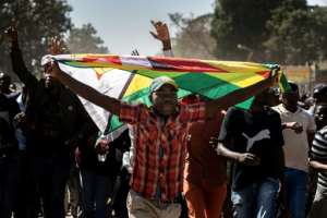 A man clutching the national flag walked with other protesters, demonstrating against the cost of living and lack of essential goods.  By Zinyange Auntony (AFP)