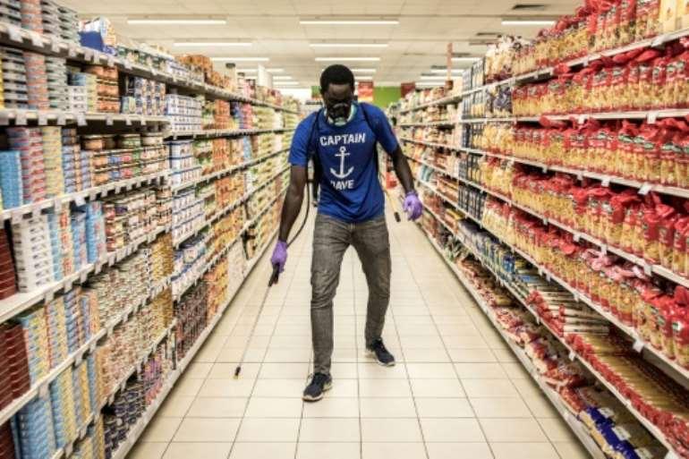 A man disinfects an empty supermarket in Dakar.  By JOHN WESSELS (AFP)