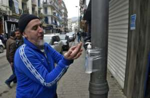 A man disinfects his hands with alcohol gel attached to a pole in Algiers.  By RYAD KRAMDI (AFP)
