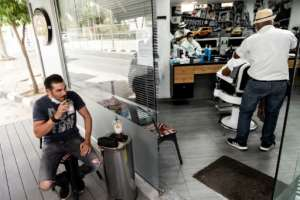 A man drinks coffee outside a hairdresser's salon in the Cypriot capital Nicosia.  By Iakovos Hatzistavrou (AFP)