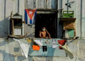 A man in a facemask stands on his balcony in Havana, Cuba.  By YAMIL LAGE (AFP)