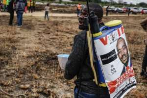 A man on his way to an election rally on July 7 with a campaign poster featuring Movement for Democratic Change Alliance leader Nelson Chamisa.  By ZINYANGE AUNTONY (AFP/File)