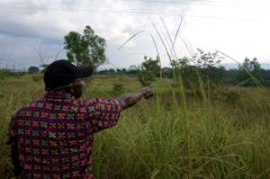 A man points at an old uranium extracting shaft in Mounana, Gabon, where hundreds of men used to work