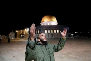 A man prays in front of the Dome of the Rock at the Al-Aqsa mosque compound, which reopened on Sunday.  By Ahmad GHARABLI (AFP)