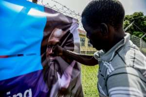 A man punches a banner bearing a picture of Dominic Ongwen.  By ISAAC KASAMANI (AFP/File)