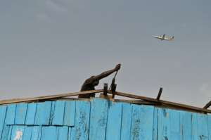 A man removes the roof of his house in Adjouffou. Authorities announced the security perimeter after a 14-year-old boy scaled a fence to climb onto the landing gear of a departing jetliner -- his tragic death also triggered a security alert.  By ISSOUF SANOGO (AFP)