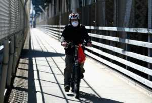 A man rides his bike over the Manhattan Bridge in New York.  By Angela Weiss (AFP)