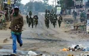 A man runs away from Kenyan security forces patrolling in a Nairobi slum following overnight demonstrations by supporters of opposition leader Raila Odinga who are demanding that President Uhuru Kenyatta's re-election be overturned