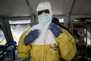 A medical worker puts on his Personal Protective Equipment (PPE) ahead of entering an Ebola Treatment Centre in Beni.  By John WESSELS (AFP/File)