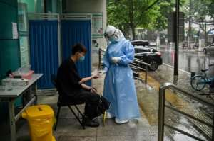 A medical worker prepares to test a man for the COVID-19 novel coronavirus in Wuhan, China.  By Hector RETAMAL (AFP)