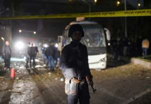 A member of the Egyptian security forces stands guard at the scene of an attack on a tourist bus in Giza province south of the Egyptian capital Cairo, on December 28, 2018.  By MOHAMED EL-SHAHED (AFP)