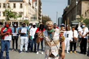 A member of the Khoisan community speaks before joining a protest march under the banner of