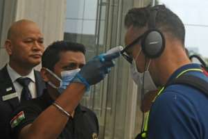 A member of hotel staff wearing a facemask amid concerns over the spread of the COVID-19 novel coronavirus checks the temperature of South African cricket player Faf du Plessis upon his arrival at a hotel in Kolkata.  By Dibyangshu SARKAR (AFP)