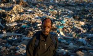A migrant wears a mask found in a rubbish dump in Fnideq, northern Morocco, on July 5, 2018.  By FADEL SENNA (AFP)