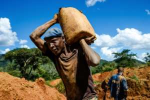A miner carries a load of ore at Manzou Farm, owned by Grace Mugabe, the wife of former president Robert Mugabe.  By Jekesai NJIKIZANA (AFP/File)