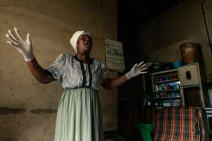 A moment for prayer: Gwena belongs to an Apostolic religious sect where she says she got her calling to take up midwifery. She says she has delivered as many as 250 children.  By Jekesai NJIKIZANA (AFP)