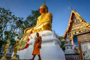 A monk walks in front of a giant Buddha statue wearing a face mask at Wat Nithet Rat Pradit temple in Pathum Thani outside Bangkok.  By Mladen ANTONOV (AFP)