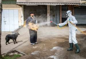A Moroccan health ministry worker disinfects a man walking a dog and carrying a mat in Rabat.  By FADEL SENNA (AFP/File)