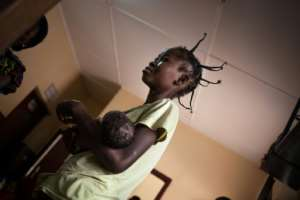 A mother waiting with her malnourished child to be weighed by doctors.  By FLORENT VERGNES (AFP)