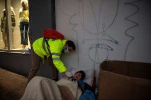 A nurse in Athens takes a swab from a homeless man for an antigenic test as Greece faces a new wave of Covid-19 infections.  By ANGELOS TZORTZINIS (AFP)