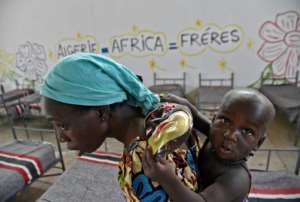 A Nigerien migrant carries her child in a transit camp in Laghouat, northern Algeria as she is repatriated on June 29, 2018.  By RYAD KRAMDI (AFP)