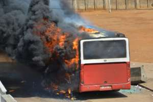 A bus was torched at the scene of the protests in Guinea's capital Conakry.  By CELLOU BINANI (AFP)