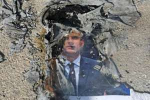 A burnt picture of French President Emmanuel Macron is seen during a demonstration against him at the Palestine Technical University near Hebron, as boycott calls on French goods grow in the Muslim world.  By HAZEM BADER (AFP)