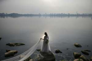 A bride poses for a wedding photographer on East Lake in Wuhan, the city where the virus first emerged in December.  By Hector RETAMAL (AFP)