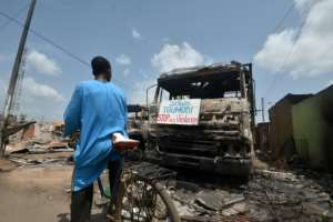 A cyclist reads a sign on a burnt truck calling for violence to stop in the market of Toumodi.  By SIA KAMBOU (AFP)