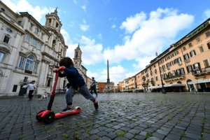 A child rides a scooter in an emptied-out square in Rome.  By Andreas SOLARO (AFP)