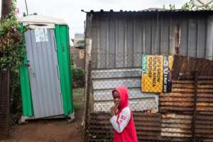 A child walks past a shack with a makeshift toilet outside and an ANC poster for May 8 elections seen as a key test of the party's ability to deliver on its post-apartheid promises.  By WIKUS DE WET (AFP)