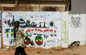 A citizen walks past recently painted murals at the protest site in Khartoum.  By Ebrahim Hamid (AFP)