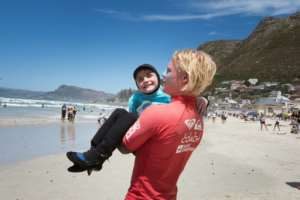 A coach carried nine-year-old JJ Booysens to the beach at a recent adaptive surfing event. By RODGER BOSCH (AFP)