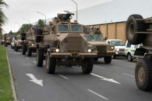 A convoy of South African army vehicles drives through a street in Cape Town as part of the deployment.  By RODGER BOSCH (AFP)