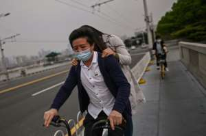 A couple wearing facemasks ride a bicycle over a bridge in Wuhan, where the new coronavirus first appeared in December.  By Hector RETAMAL (AFP)