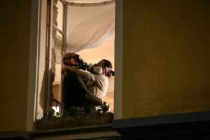 A couple in masks embrace at their window during the daily 8 o'clock applause in support of medical workers in the French Riviera city of Nice.  By VALERY HACHE (AFP)